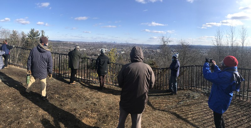 Group of people on a hill overlooking Boston in the distance